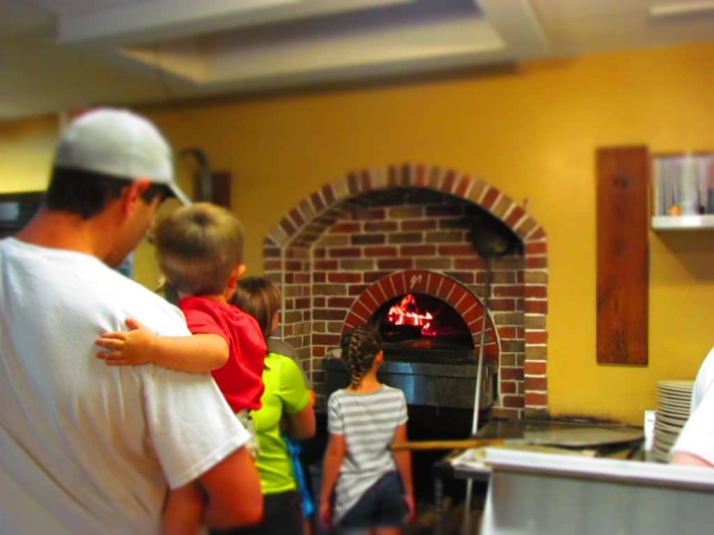 A family watches the pizza cook.