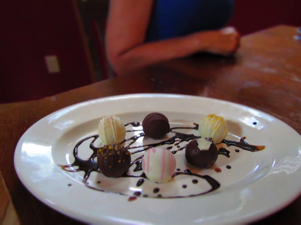 A plate of six chocolate coated cake truffles is decorated with drizzled chocolate.