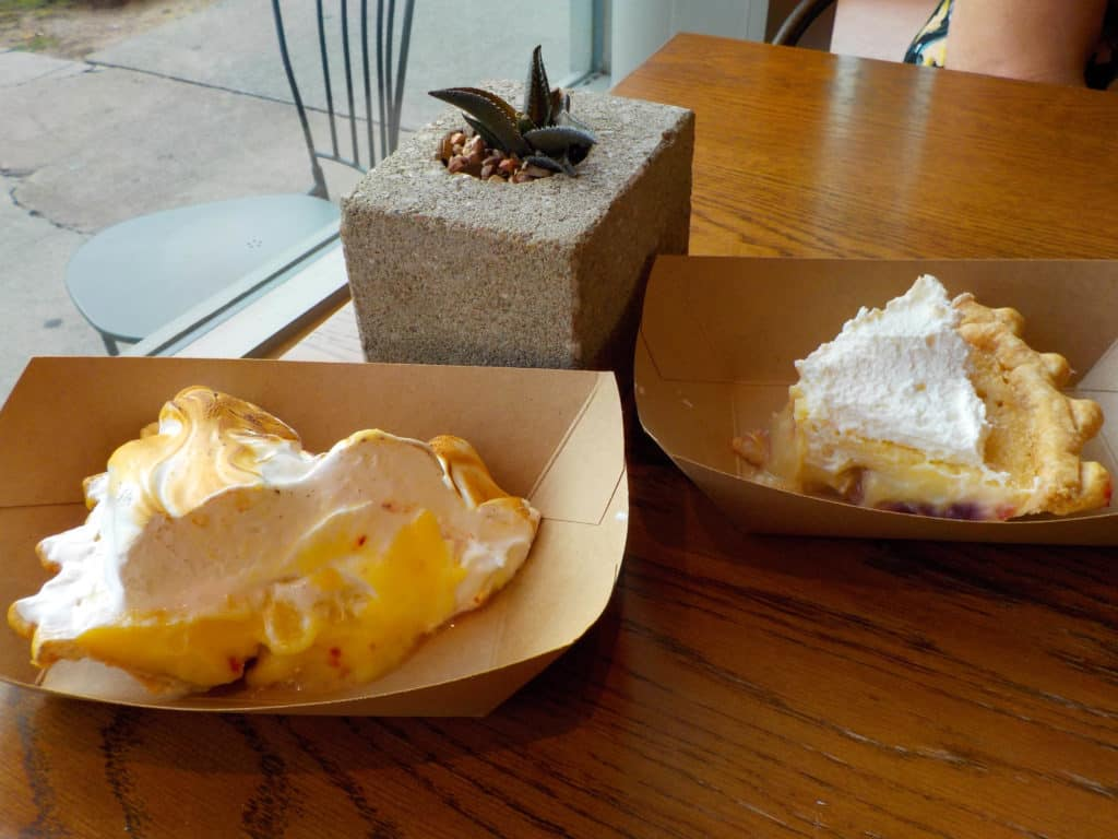Slices of pie are stacked high with meringue and whipped cream.