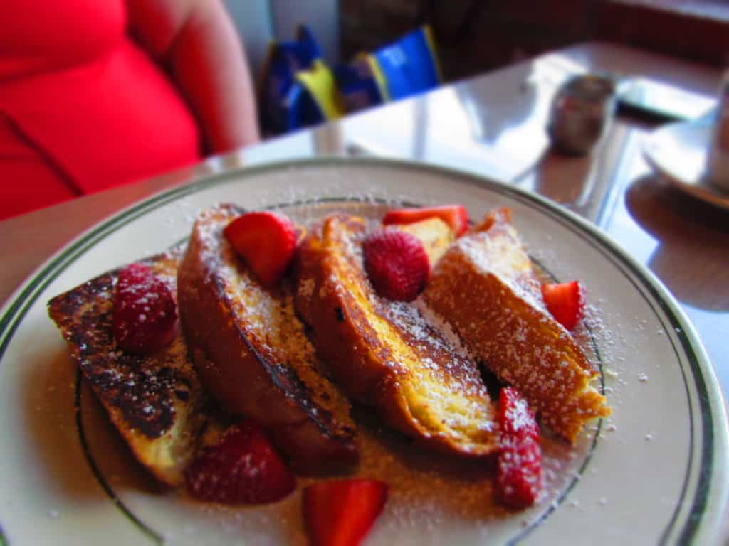A plate filled with delicious Brioche French Toast topped with powdered sugar and sliced strawberries.