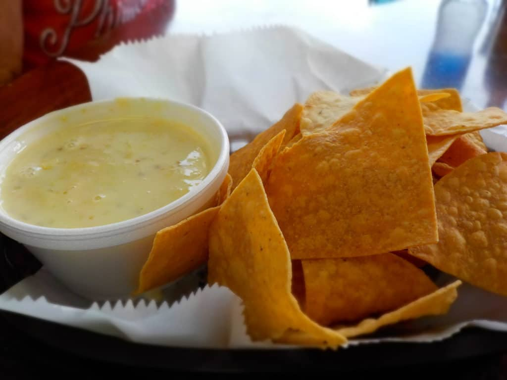 A bowl of Queso cheese dip is served with crispy tortilla chips.