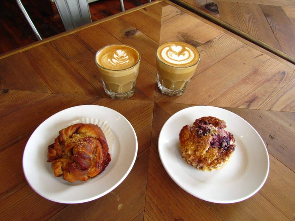 Pastries and coffees are displayed on a par quay wooden table top.