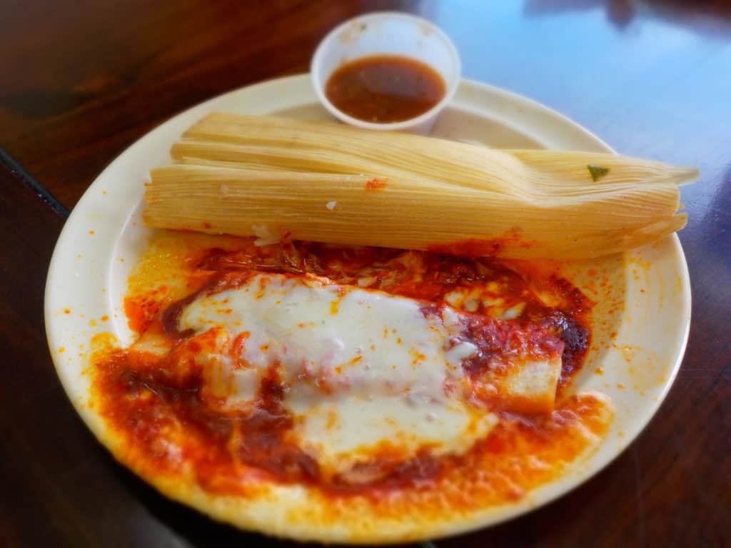 A tamale and enchilada share a plate.