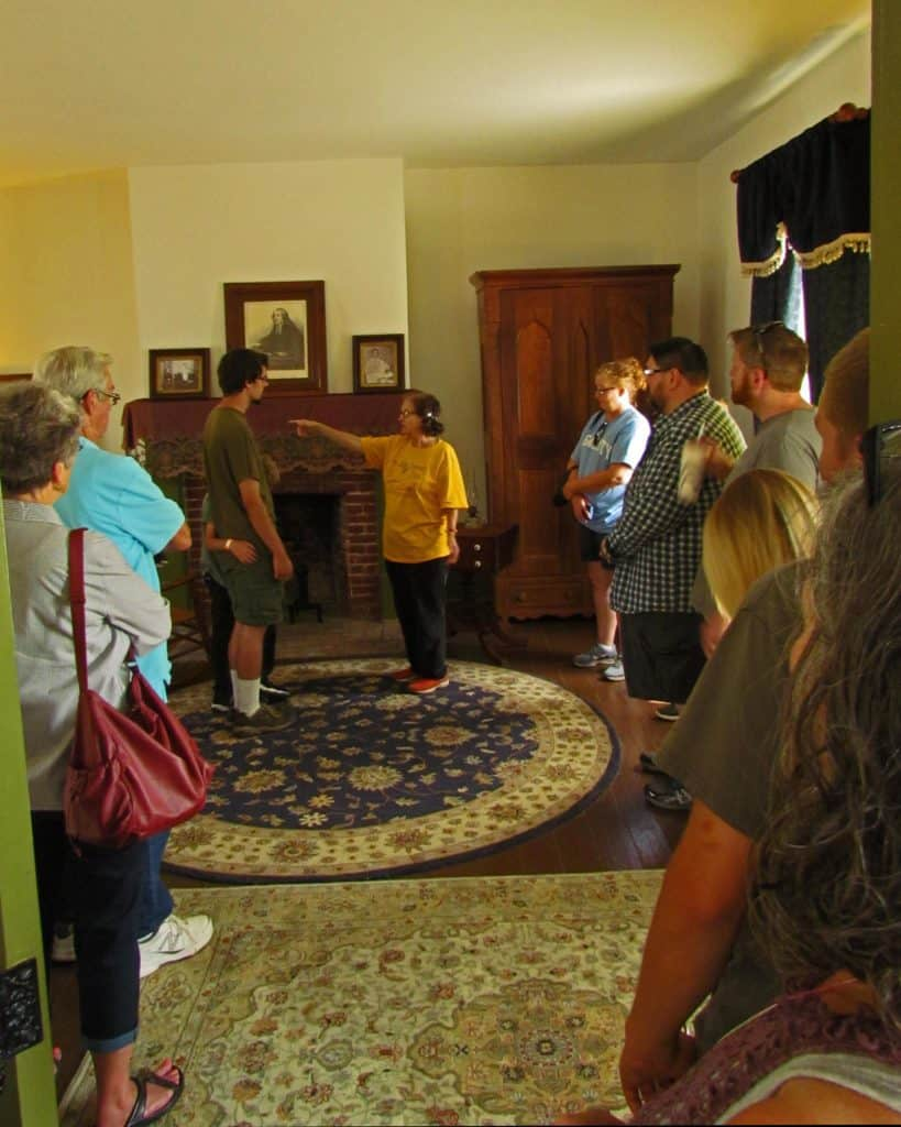 The tour guide points out interesting facts about the Grinters and their home in Wyandotte County.