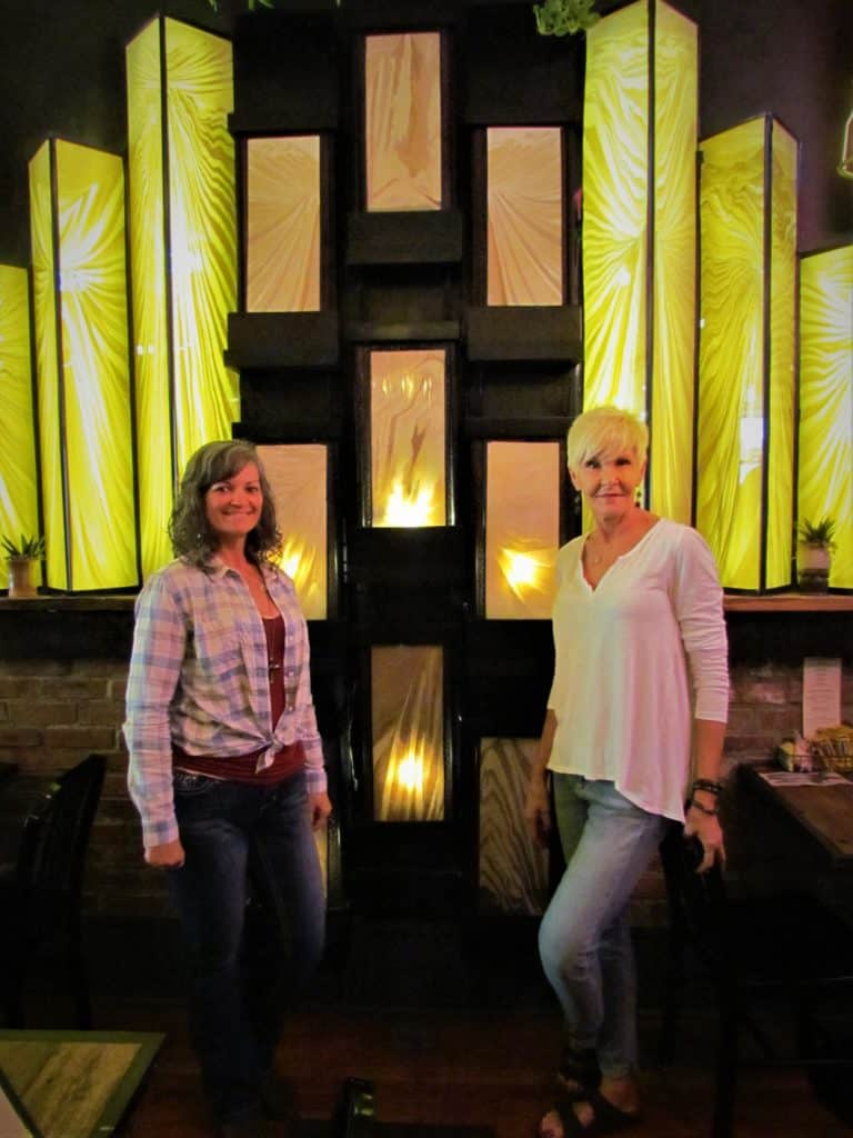 Crystal and Bobbie pose in front of a one-of-a-kind stained glass water feature.