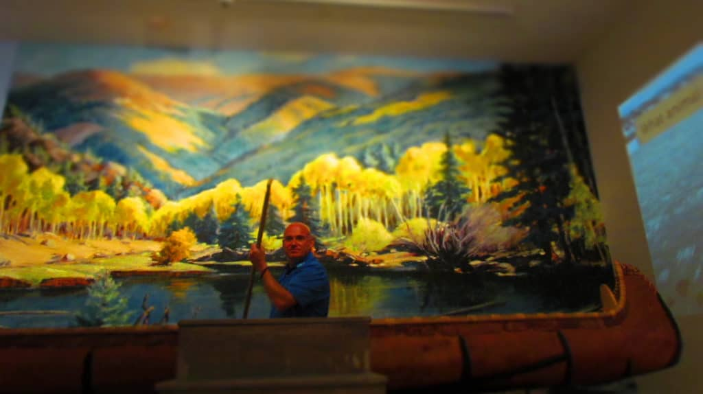 The author poses in a canoe poised in front of a scenic mural.