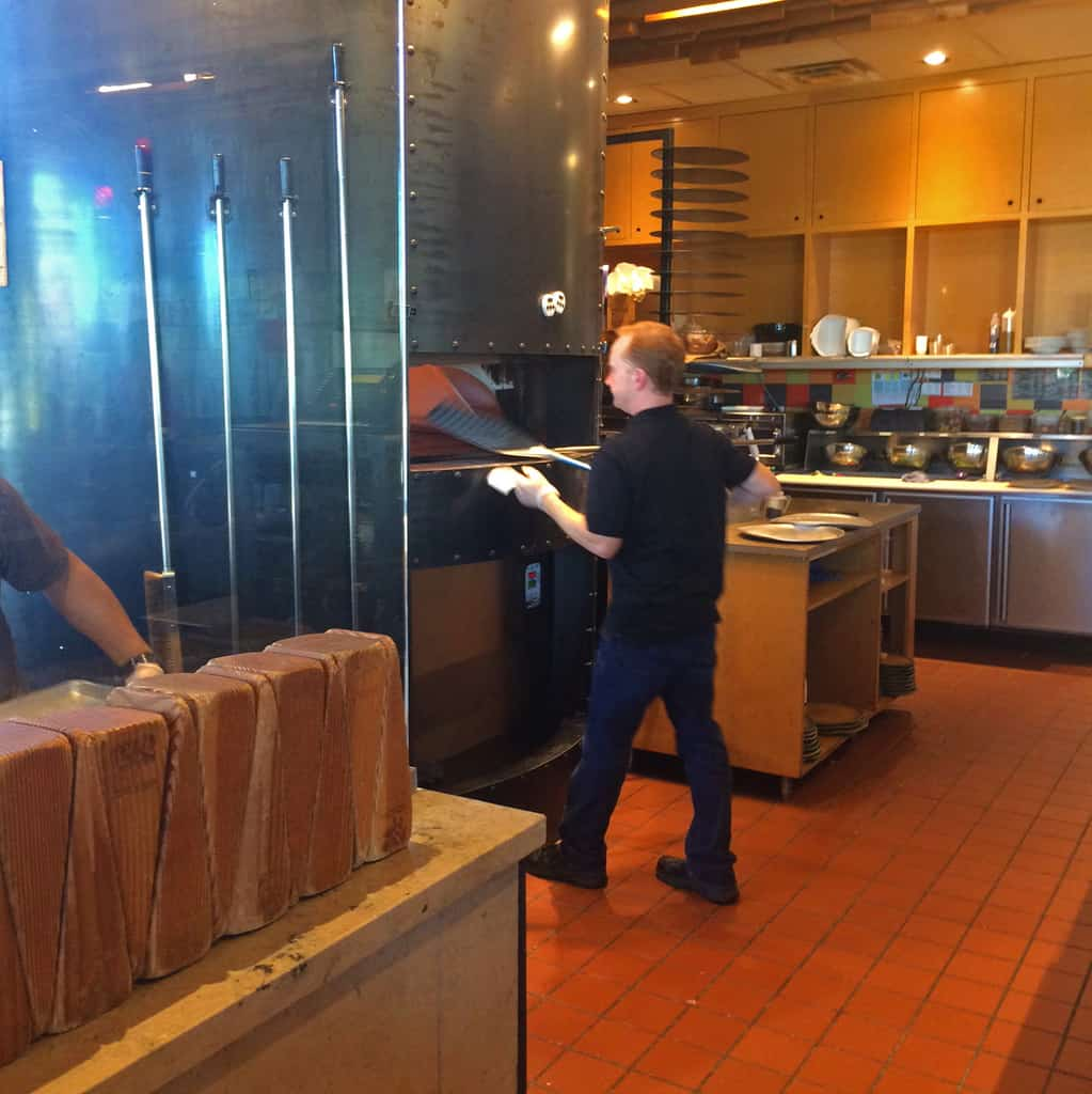 A staff member checks the pizza pies in the wood fired oven at Spin Pizza.