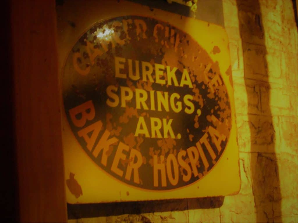 A fading signn from the Baker Cancer Hospital that once occupied the 1889 Crescent Hotel and Spa building.