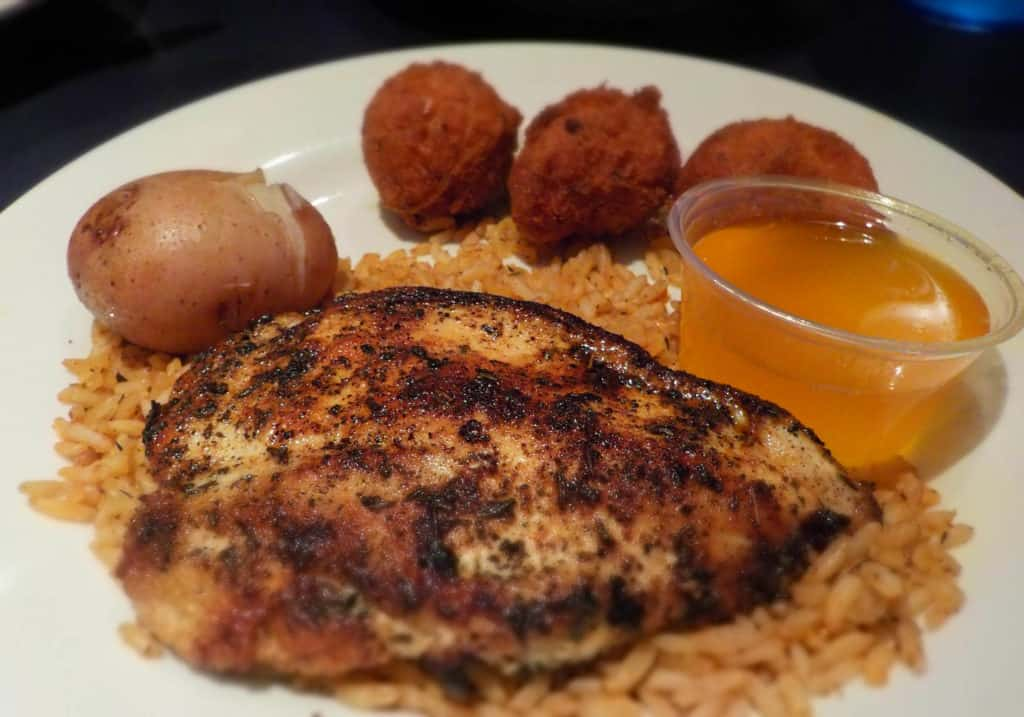 Blackened chicken rests on a bed of dirty rice.