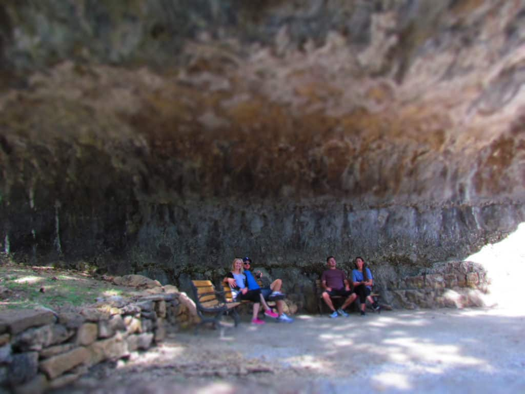 Visitors to Blue Spring Heritage Center take a short rest under the overhanging rock shelf.
