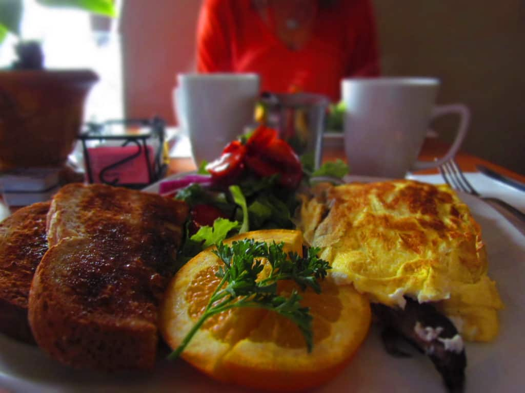 A mushroom and goat cheese omelet is the main course on a breakfast filled with salad and wheat berry toast.