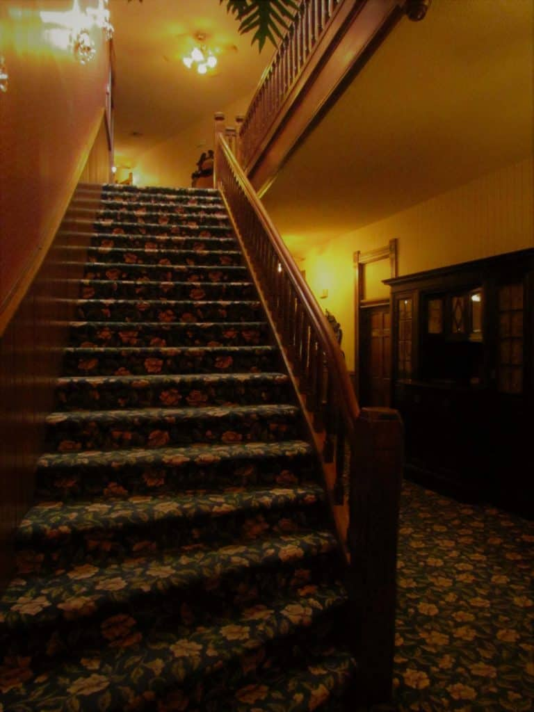 The century old staircase is bedecked with a Victorian floral carpet.