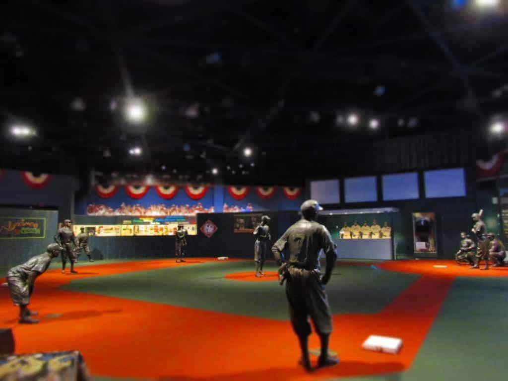 Visitors to the Negro Leagues Baseball Museum work their way through the exhibits until they reach the field of iconic players represented with life-size statues.