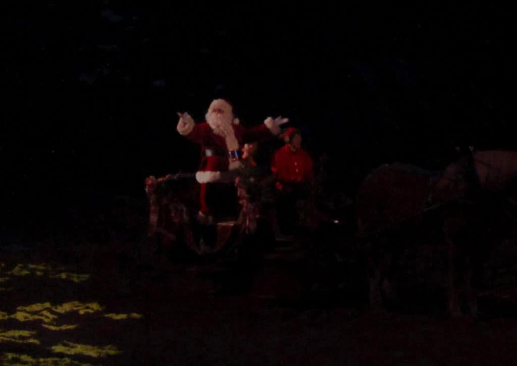 Santa arrives by sleigh to greet the crowd.