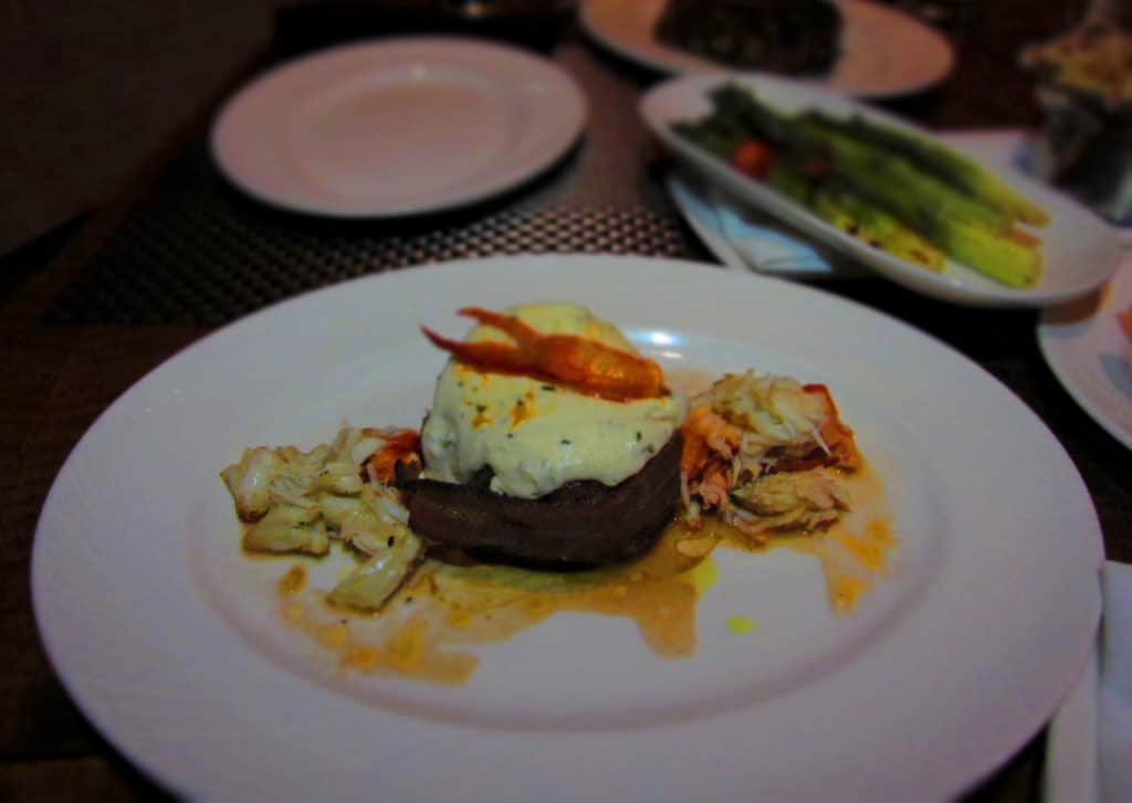 The Filet Mignon is wrapped with bacon and topped with cheese, crab, and lobster.