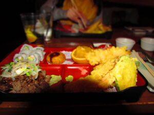Beef teriyaki bento meal also includes sushi, and tempura veggies.