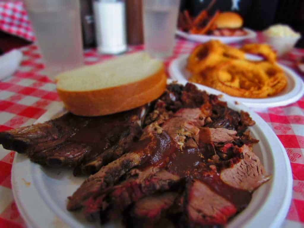 Combo platter featuring ribs, burnt ends, chicken, and sliced beef brisket is accompanied by a side order of crispy onion rings.