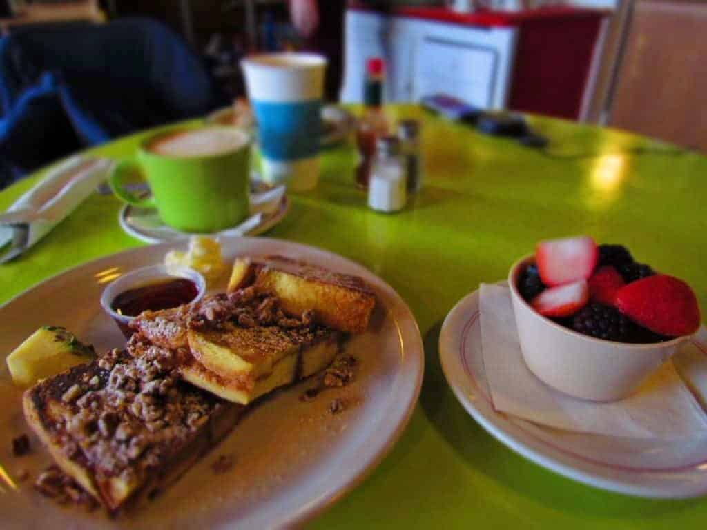 A sweet serving of French Toast is accompanied by a bowl of fresh fruit and a hot cup of latte.