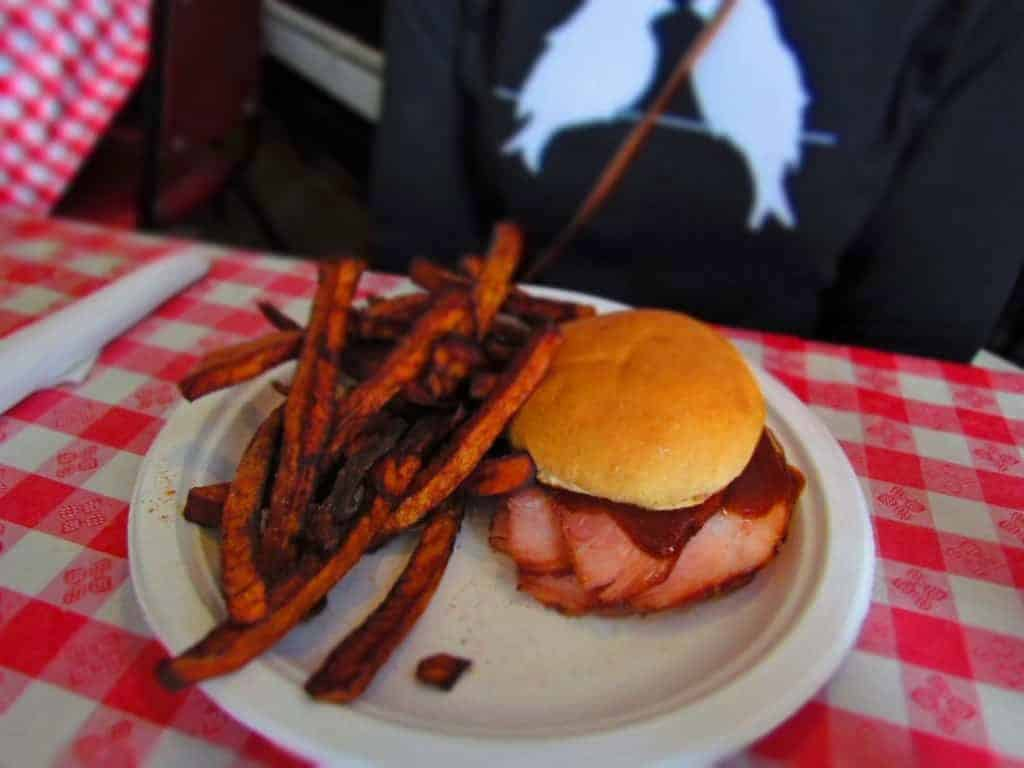 Ham sandwich with a side of sweet potato fries.