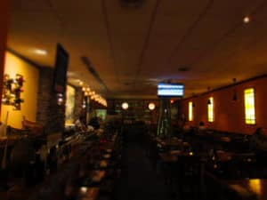 The interior of Wa restaurant is filled with tables, as well as a long seating area in front of the sushi bar.