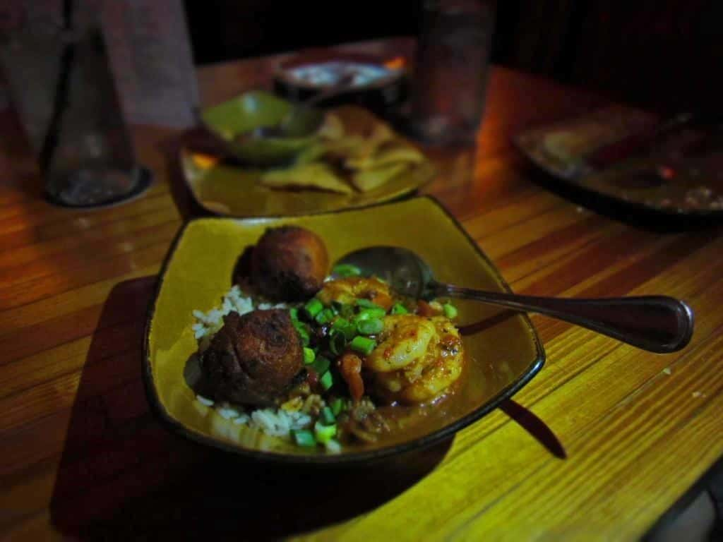 A bowl of shrimp etouffee is combined with spicy hushpuppies.