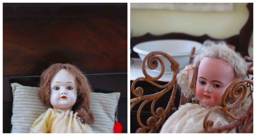 Two old dolls are on display in the living quarters of the old prairie house.