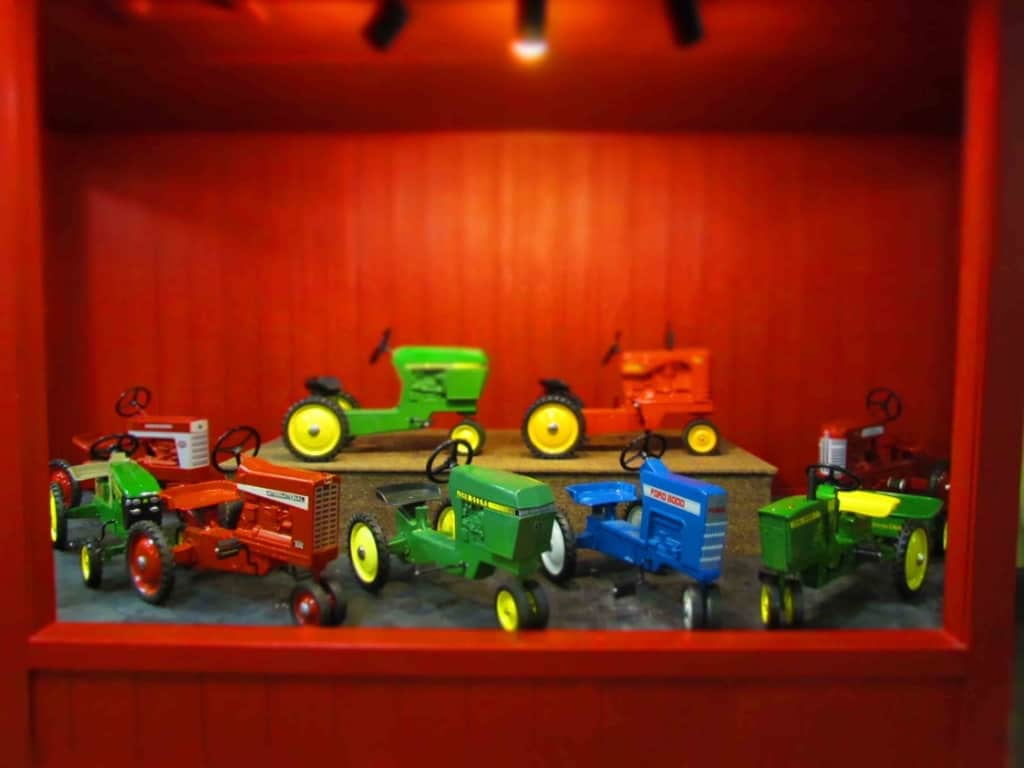 A display of pedal tractors are brightly colored and appealing to kids of all ages.