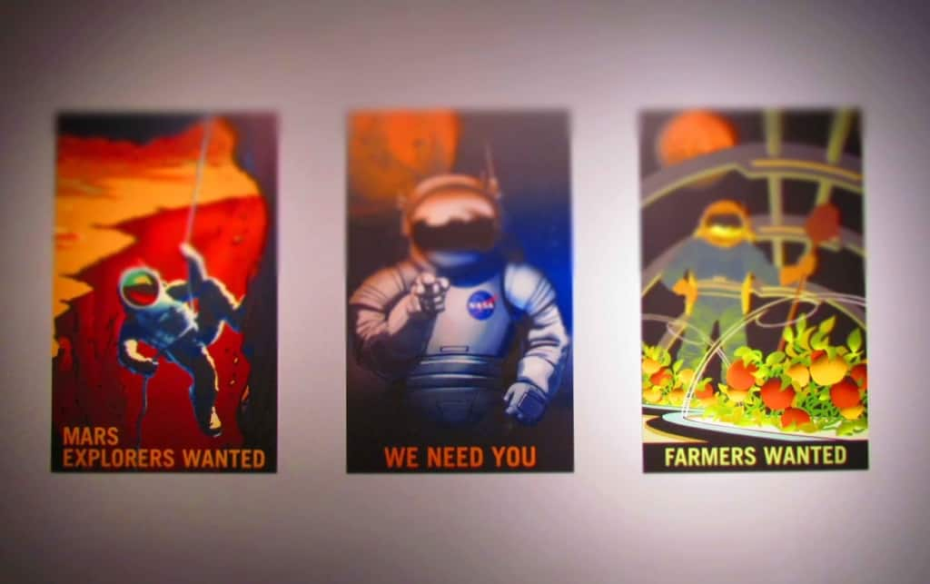 A series of mock posters advertise the need for participants to travel to Mars.