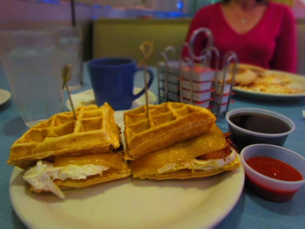 The Finals Breakfast Sandwich packs breakfast items between waffles and adds some sweet and spicy sauces for extra flavor.
