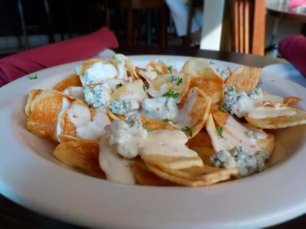 Homemade potato chips coated with a creamy garlic cheese sauce makes an excellent start to a meal.