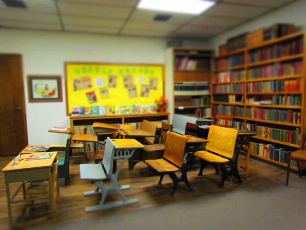 A recreated school classroom is filled with a variety of old school desks.
