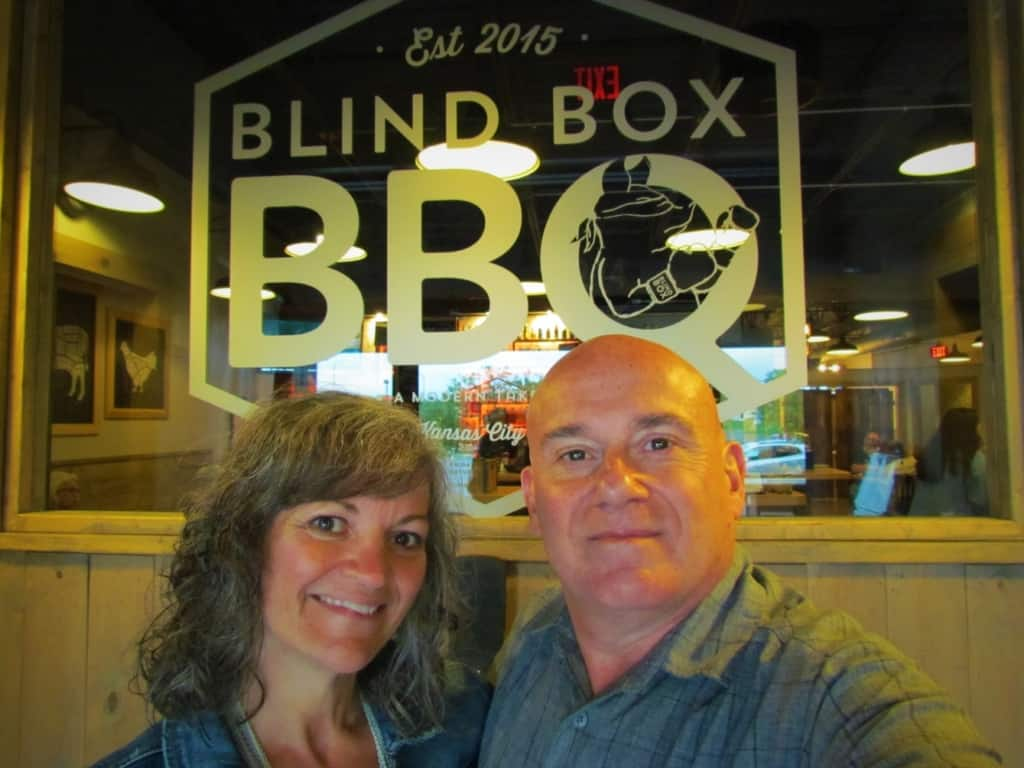 The authors pose for a selfie in front of the Blind Box BBQ logo.