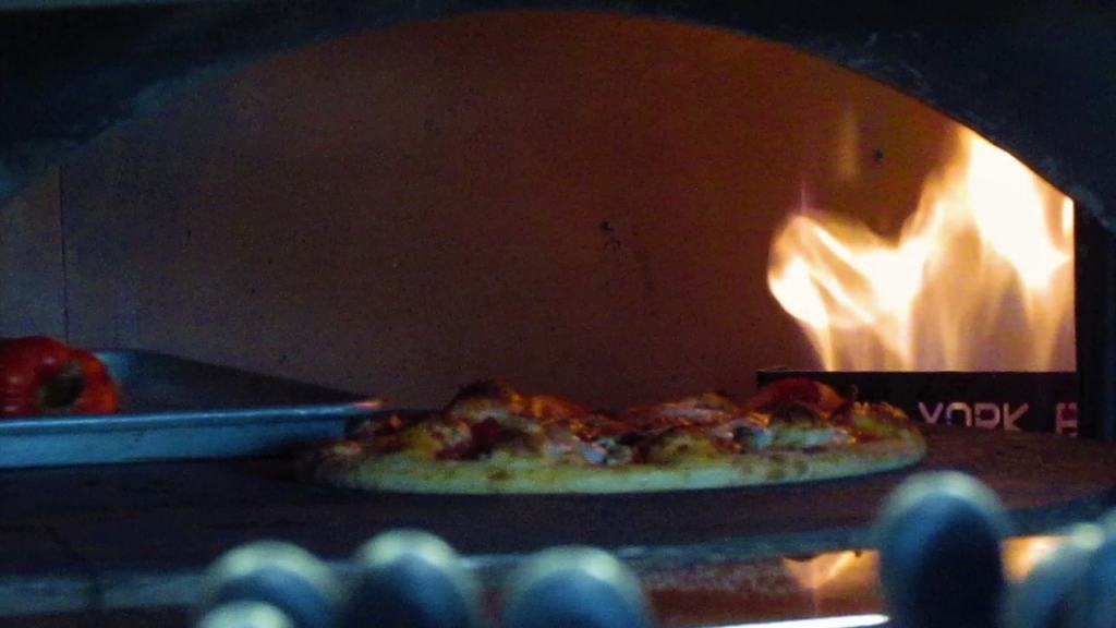 The wood fired oven cooks pizzas to perfection.