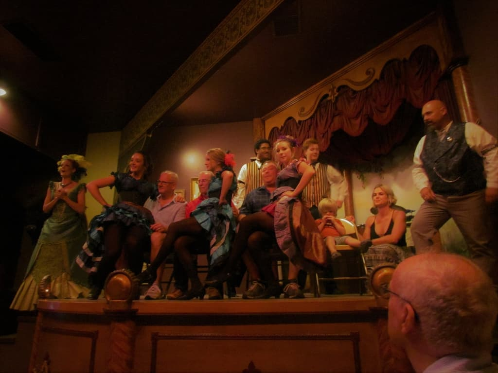 The crowd is engaged at the dance hall show in the Longbranch Saloon.