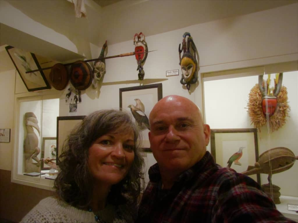 The authors pose for a selfie in front of some of the artifacts at the Martin and Osa Johnson Safari Museum.