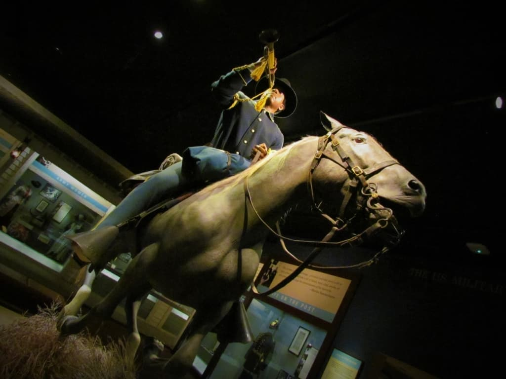 An Army soldier is poised on a horse in a recreation of a scene from the Wild West.