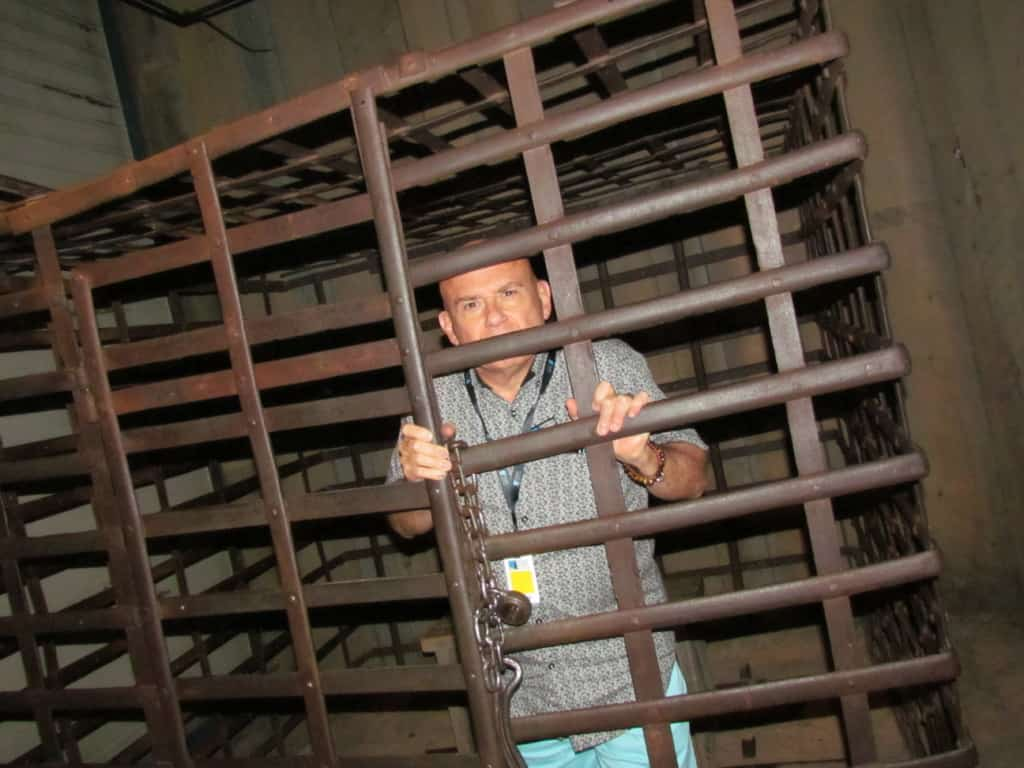 The author poses inside of a jail cell used in the displays.