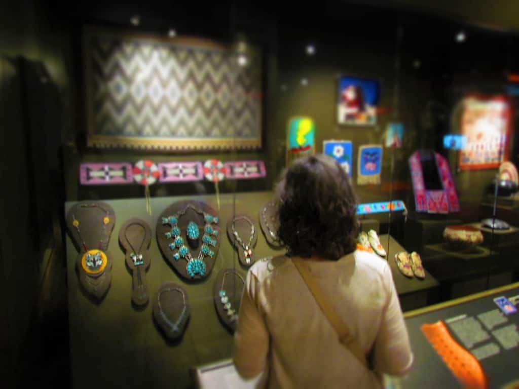 The author poses in front of a display of Native American jewelry and beadwork pieces.
