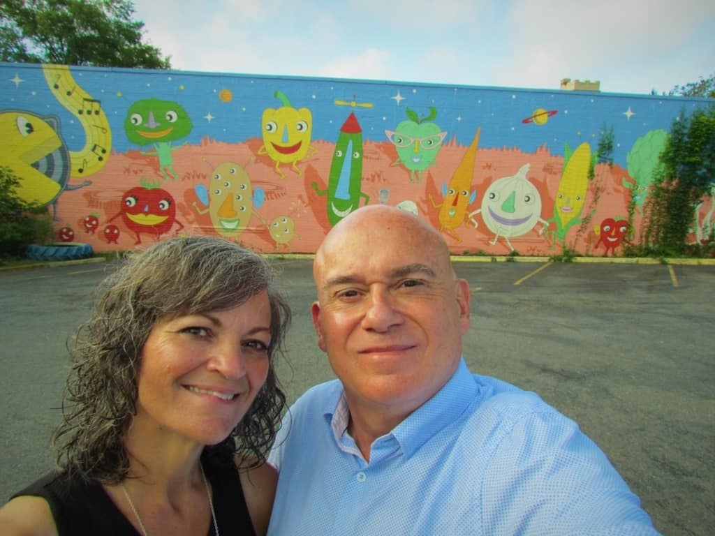 The authors pose for a selfie in front of the iconic mural located at The Root Cafe in Little Rock, Arkansas.