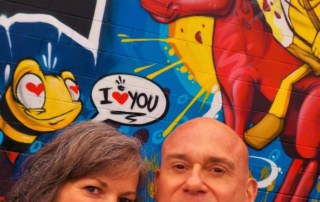 The authors pose in front of a Kansas City mural.
