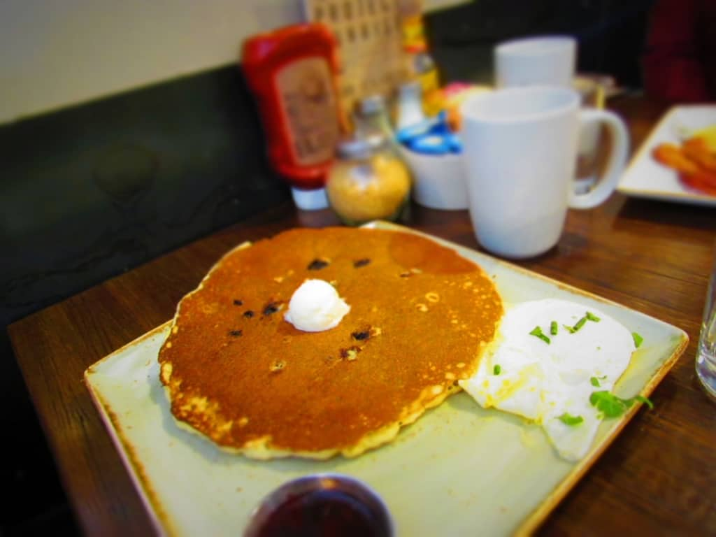 Blueberry Pancakes are served with a dressing of blueberry compote.