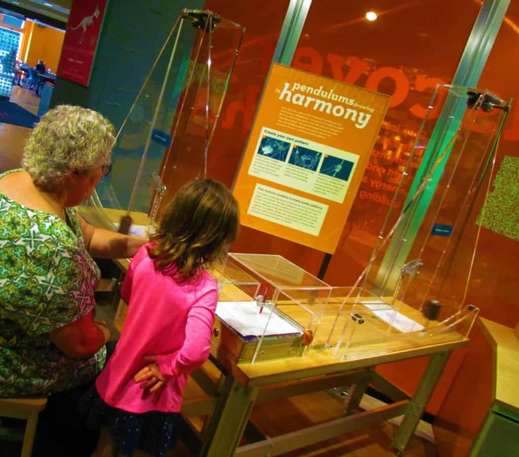 Tow museum patrons take a turn at the pendulum to create a one of a kind piece of art.