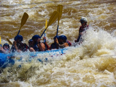 A boat team gets drenched as they hit a turbulent spot in the river.
