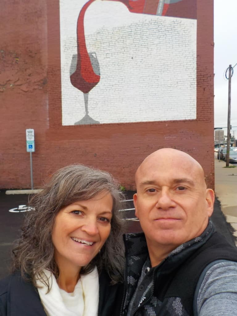 The authors pose in front of a wine mural in Kansas City, Missouri Crossroads District.
