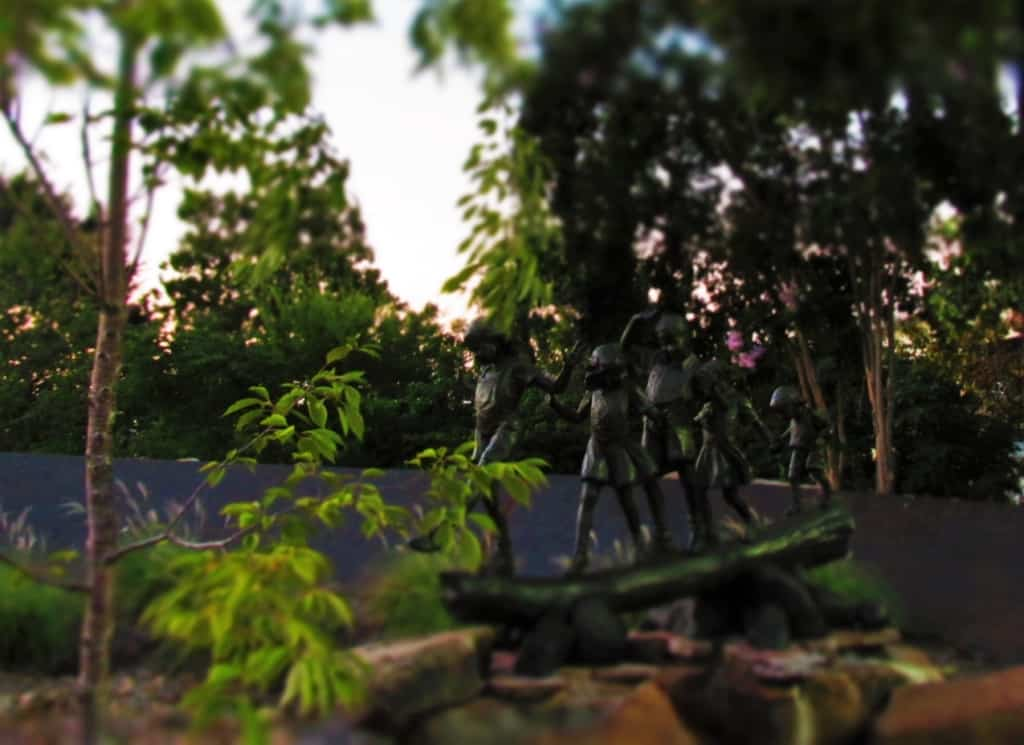 A statue in the Arkansas River Trail has a grouping of children crossing a log bridge.
