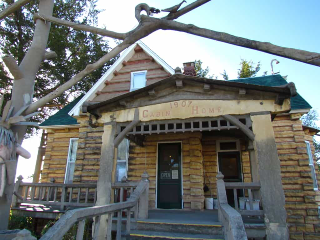 """The limestone """"log"""" cabin that Dinsmoor constructed to show tourists to Lucas, kansas."""