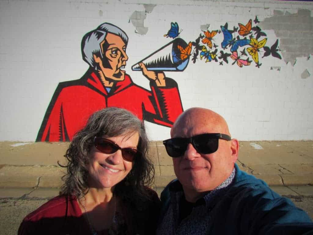 The authors pose for a selfie in front of one of the Grassroots Art Central pieces in Lucas, kansas.