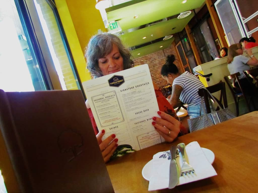 Crystal scans the menu at Tupelo Honey Cafe to select the perfect lunch trio.