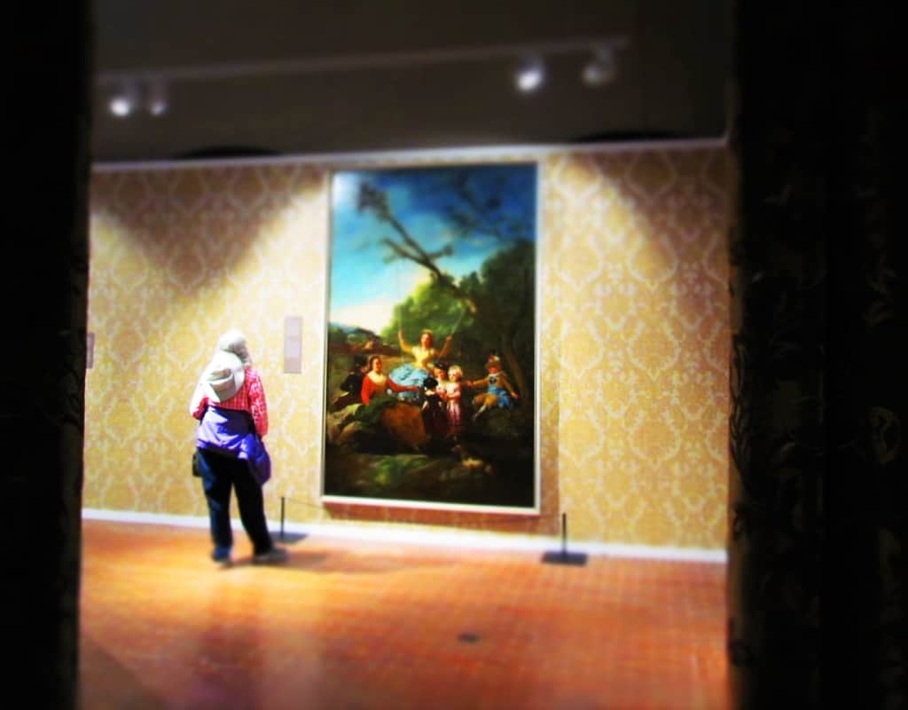 A visitor to the Cabildo examines a painting.