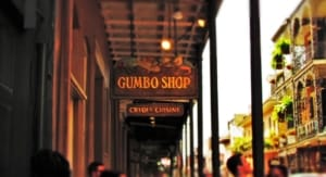 The sign for the Gumbo Shop Restaurant hangs from the balcony above.